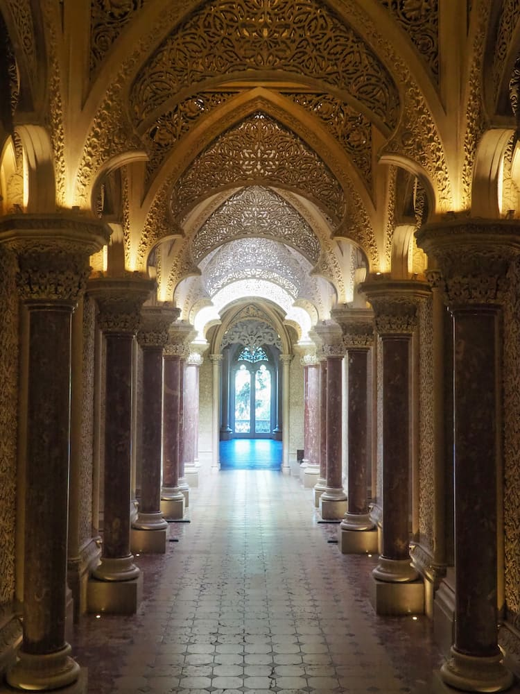 A hallway with a golden arched ceiling and marble pillars either side
