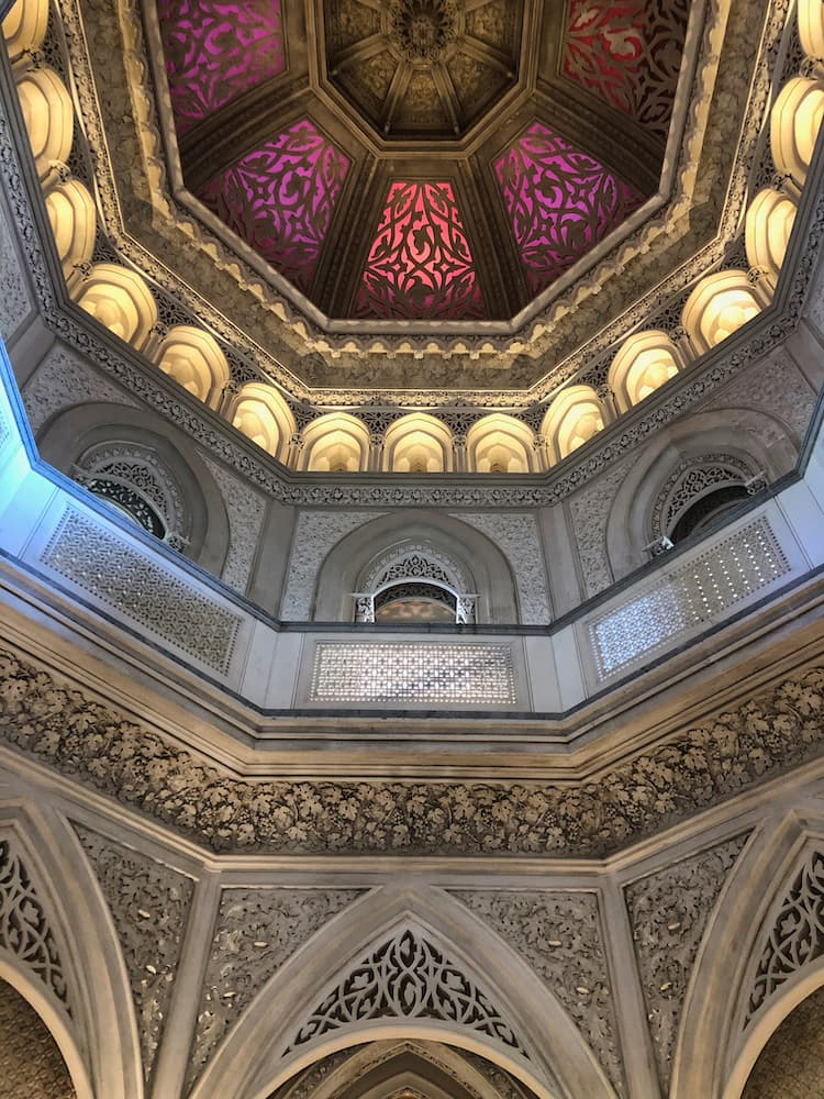 Internal view of a purple coloured dome ceiling leading down to a silver and gold wall with intricate carvings