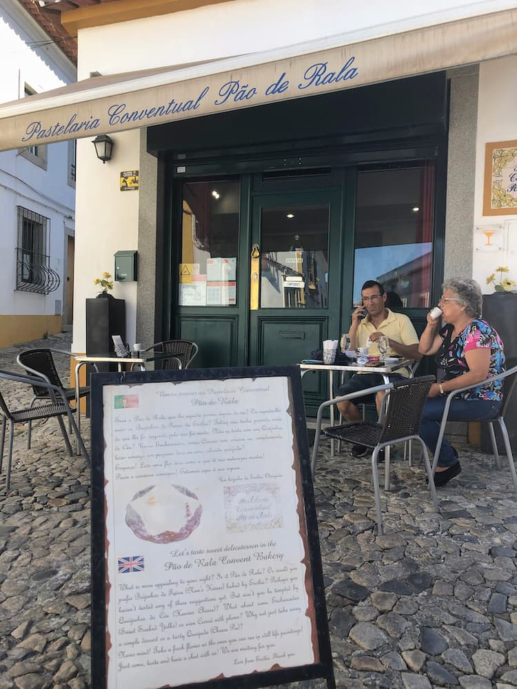 2 people sitting outside a cafe