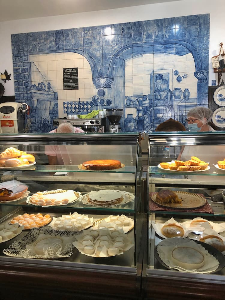 Interior of †he cafe with blue tiles on the back wall and assorted pastries in a display cabinet