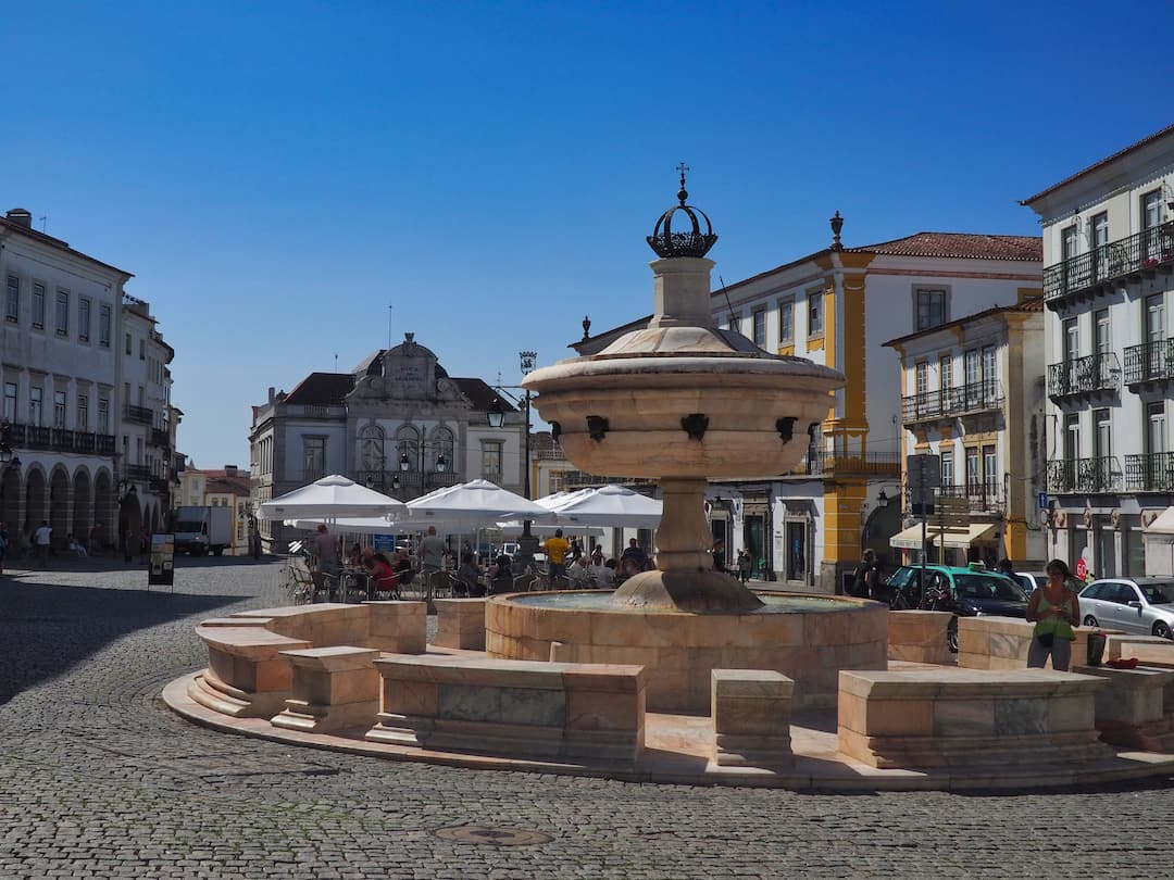 A circular stone fountain in the foreground and buildings in the background