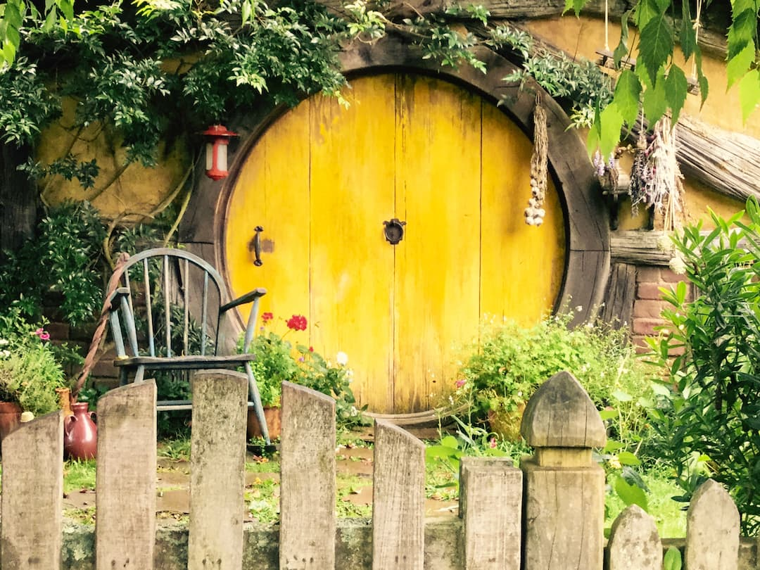A circular yellow wooden door sits behind a garden fence and a wooden chair