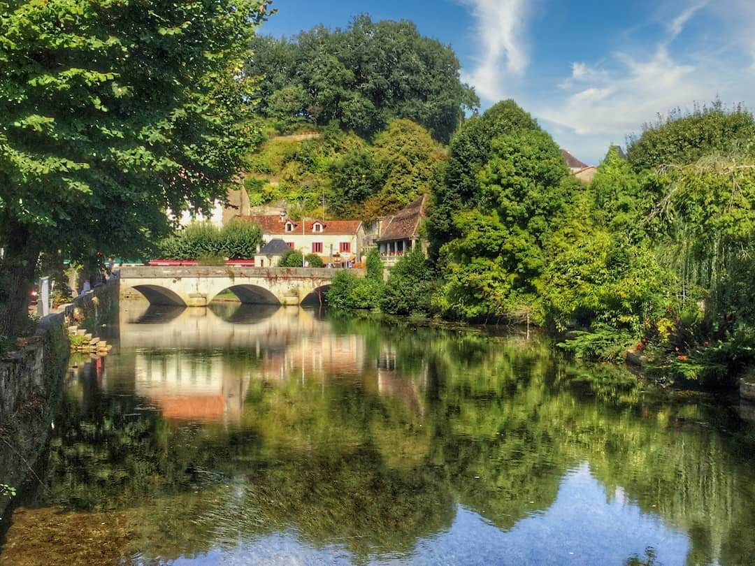 A bridge stretches across a river with its reflection and surrounding trees in the water