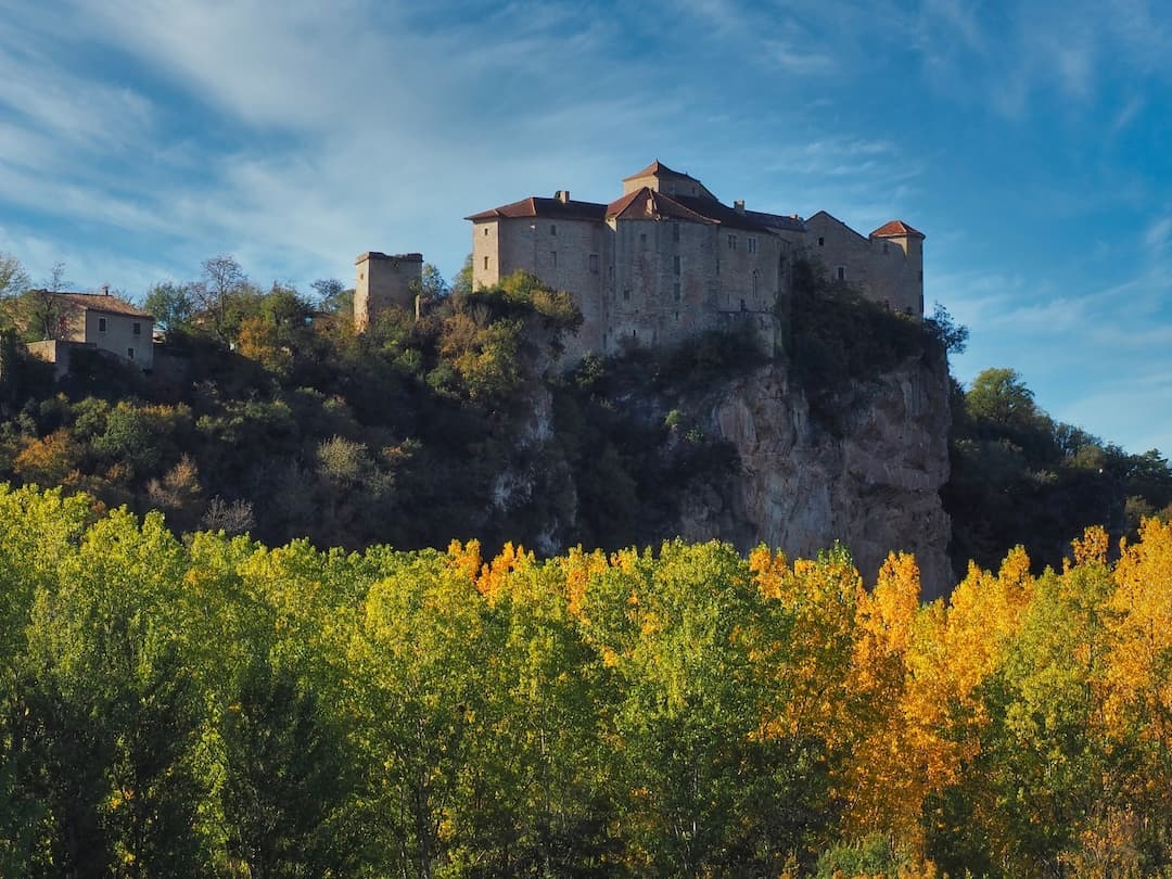 A stone village sits atop a hill with autumnal trees in the foreground