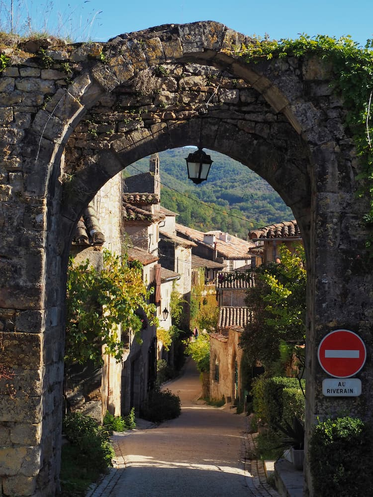 A stone arch leads through to a medieval street