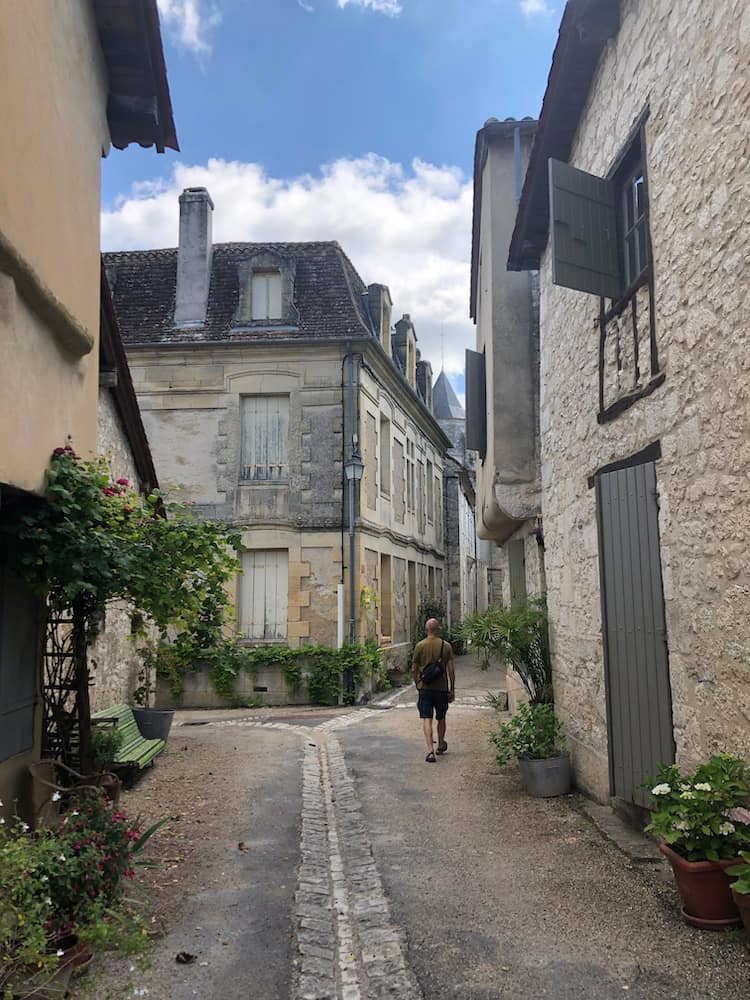 A man walks alone in a cobbled street with stone buildings on either side