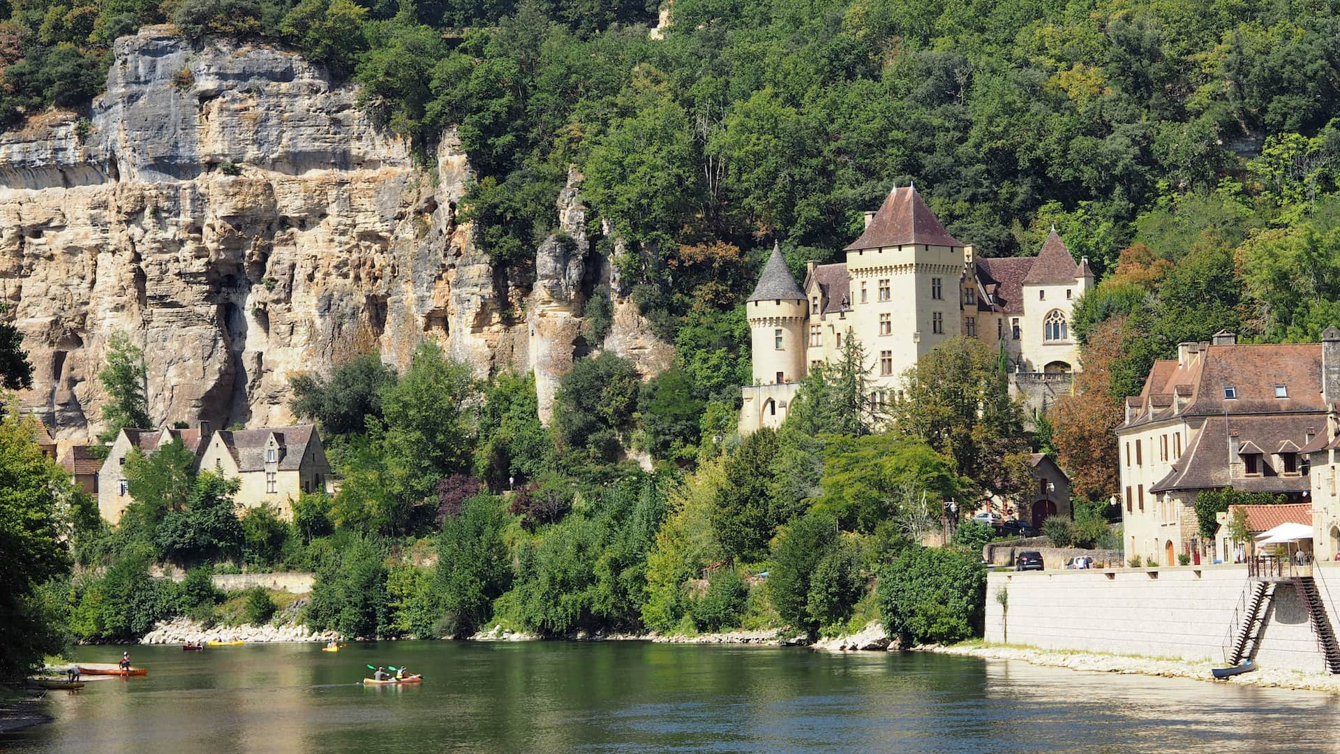 A large building with turrets looks our over a river with cliffs to the side