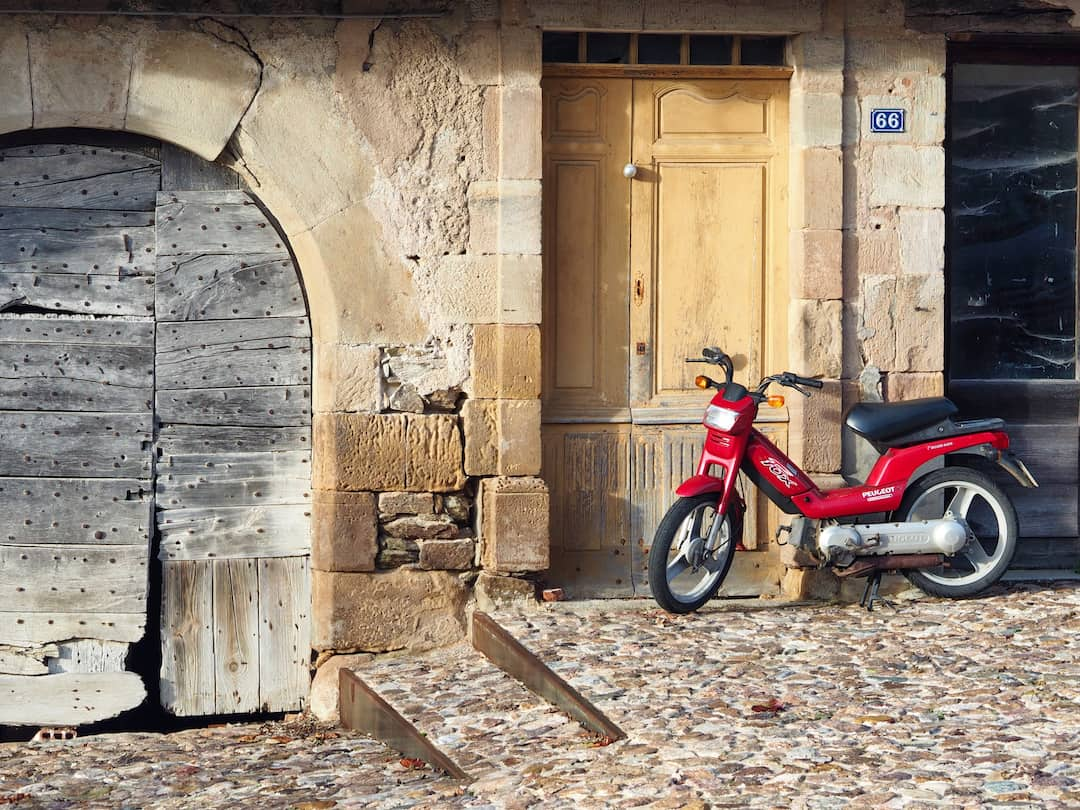 A red scooter rests against an old wall, next to a arched wooden doorway