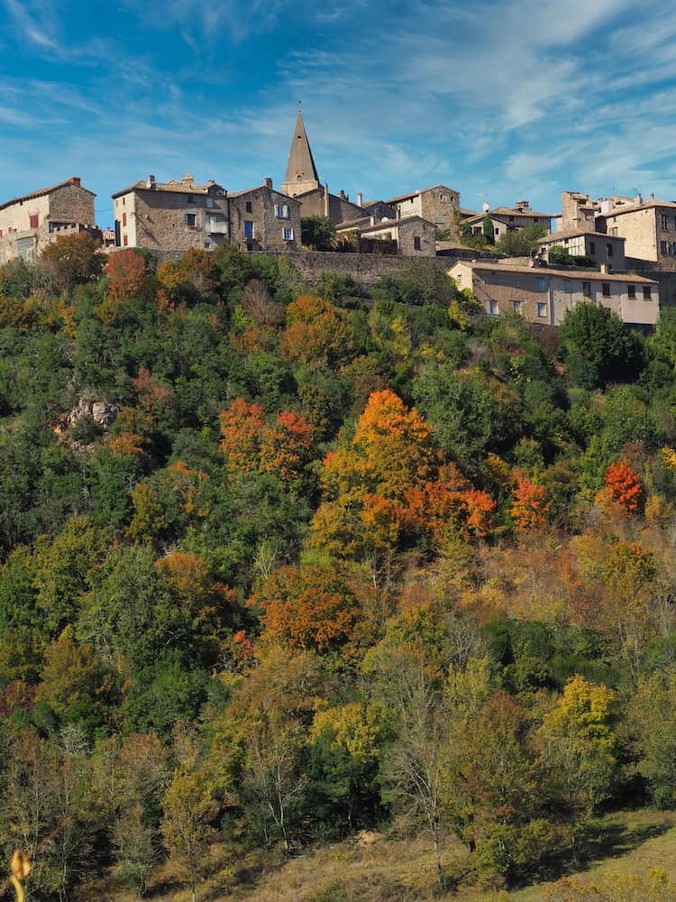 An old stone-built town looks out over a hillside of autumnal trees