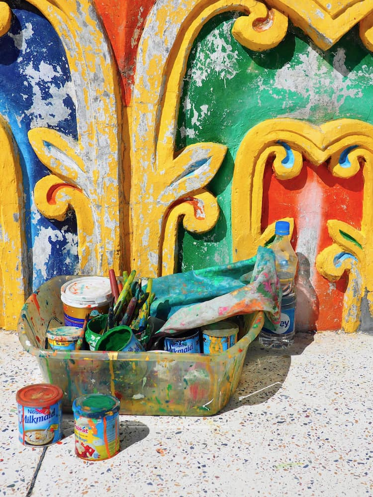 Pots of paint in front of a building wall coloured red, blue, green and yellow