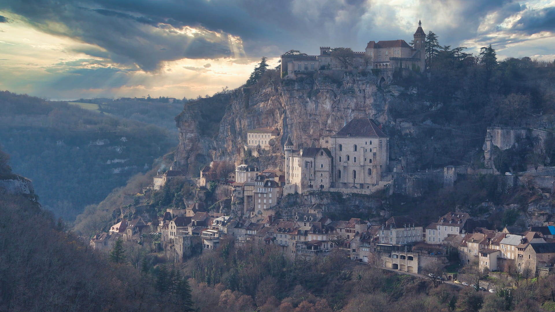 Stone houses cling to a hillside with a castle at the top, cloudy skies