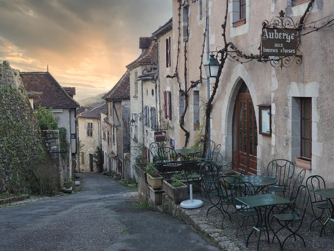 A street or stone houses runs downhill, right to left, to a sunset with green chairs in the foreground