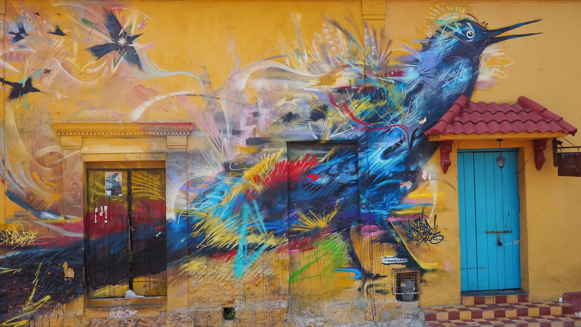 A painting of a blue bird on a yellow wall