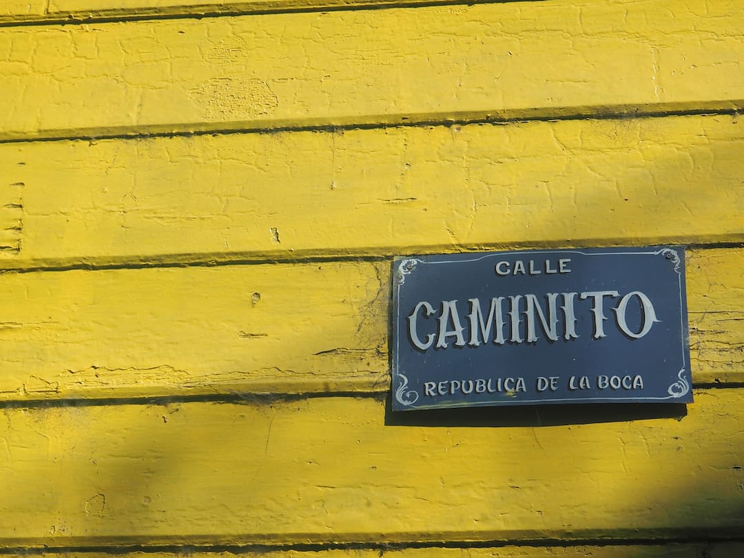Yellow wooden panels with a grey street sign bottom right