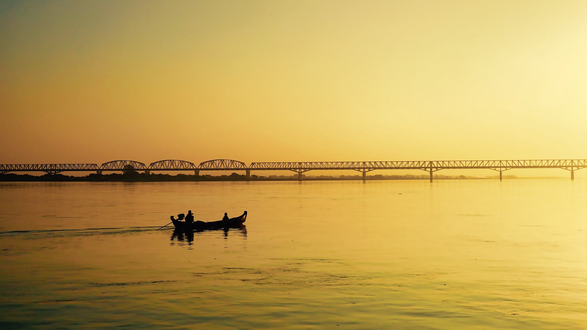 A small boat and a bridge are silhouetted against a yellow background of the sky and river