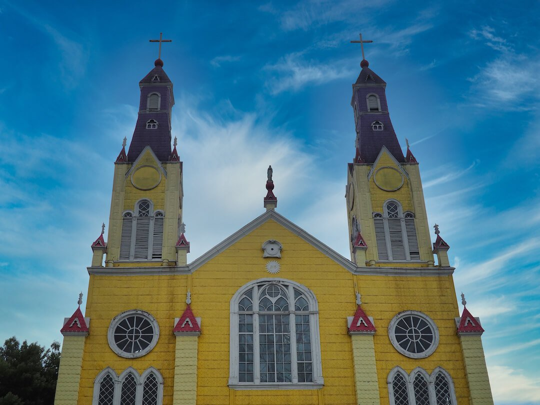 A yellow wooden church with two towers on each side with a blue sky behind