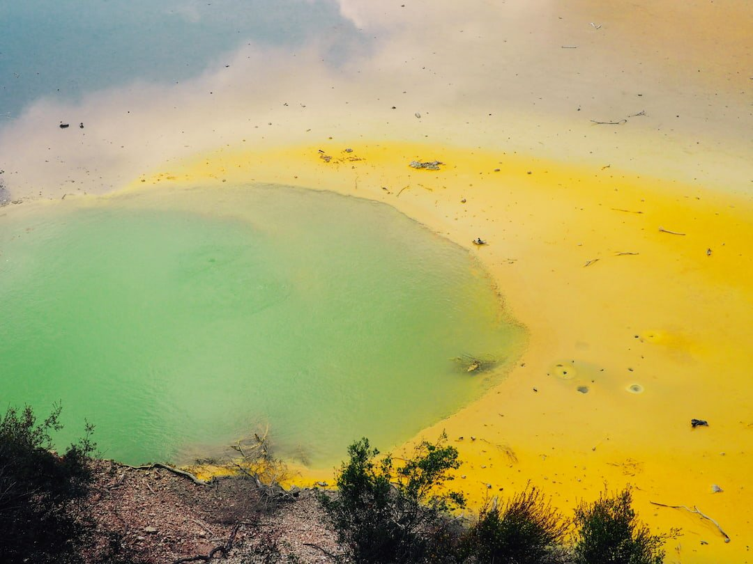A pool of water coloured green and yellow with a reflection of blue sky and clouds