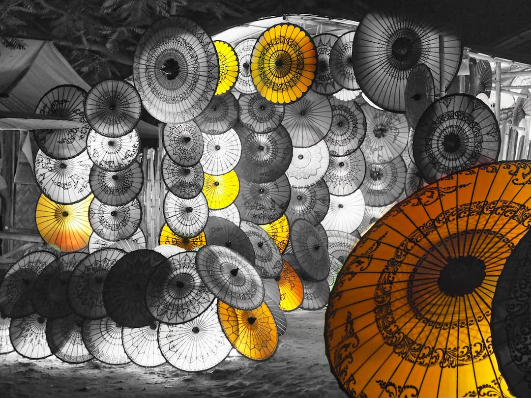 Monochrome image of lots of umbrellas stacked upon one another with the yellow ones appearing in colour