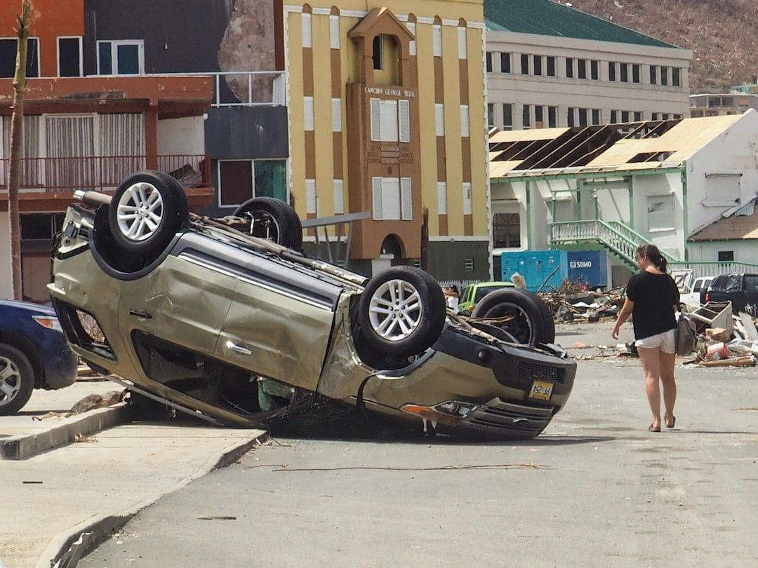A woman walks past an overturned car