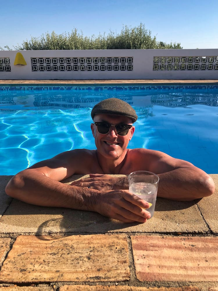 Ian with a drink inside a swimming pool
