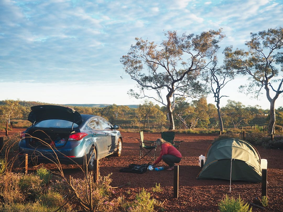 Nicky prepares a campfire in between a car and a small tent