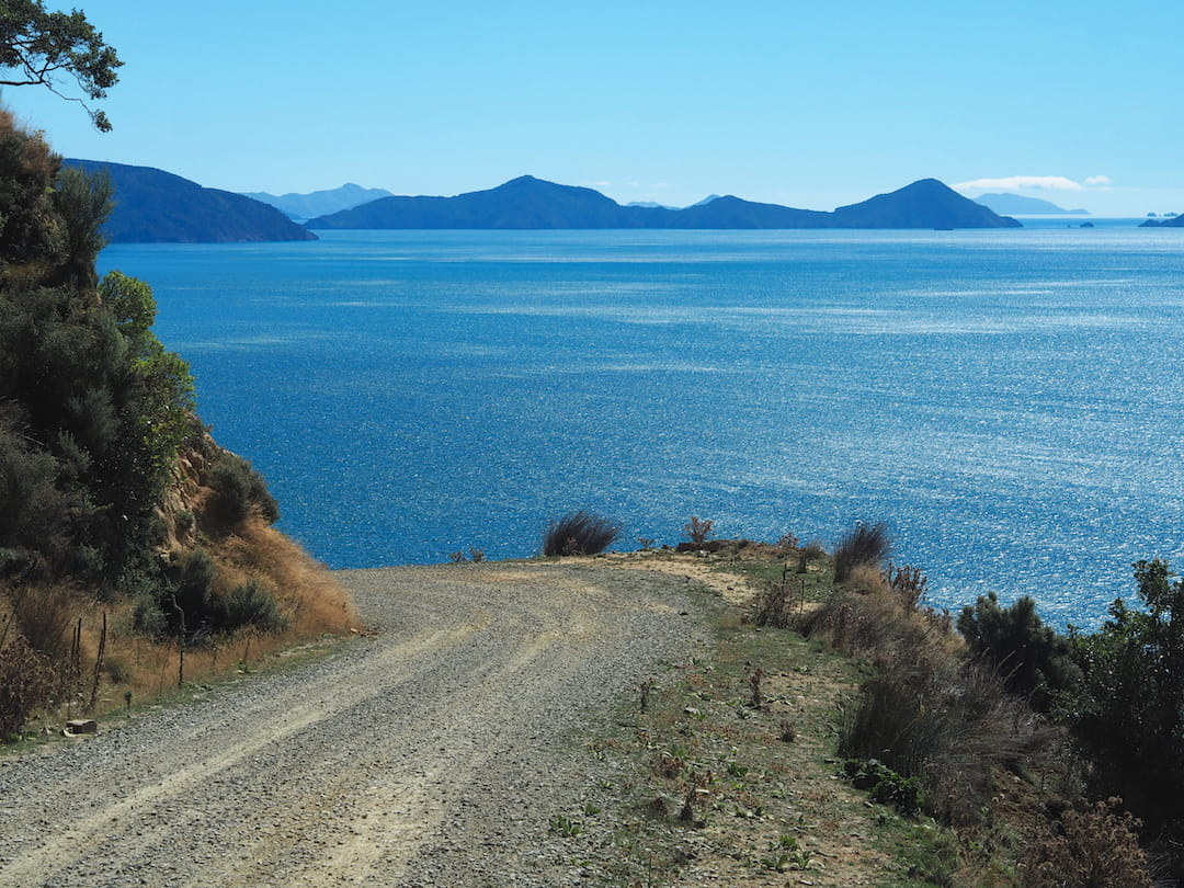 A gravel road turns to the left on a hillside overlooking the sea, with mountains in the distance
