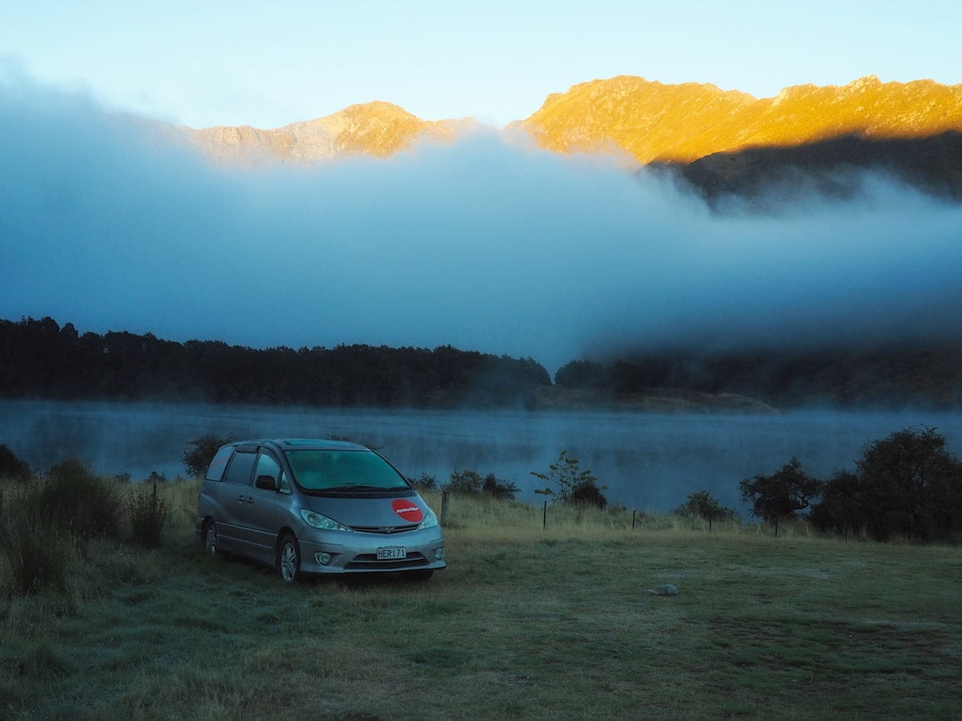 A car is parked on frosty ground beside a lake, with mist and mountains behind
