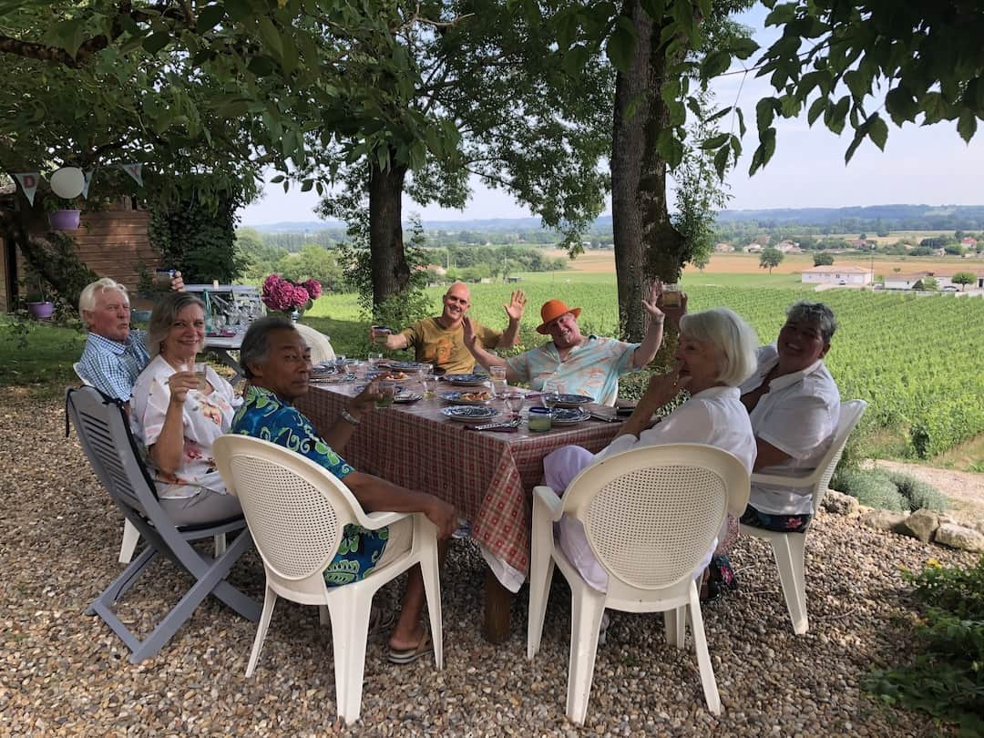 A group of people sit around an outdoor table and chairs overlooking a vineyard