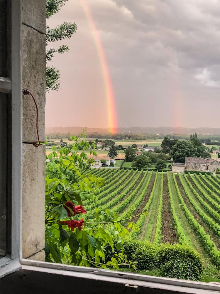 Looking out of an open window over a vineyard with a rainbow to the left