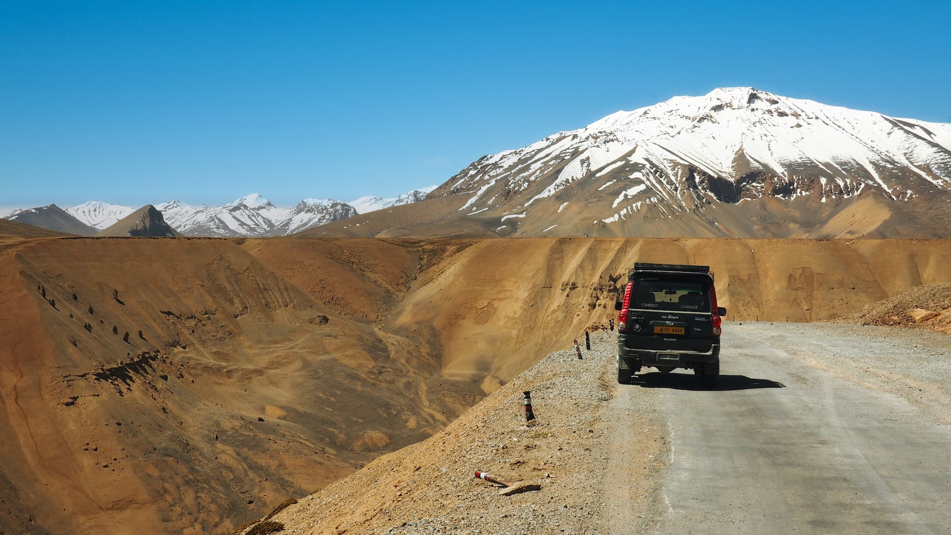 A car is parked on the side of a mountain road with a snow-capped peak in the background