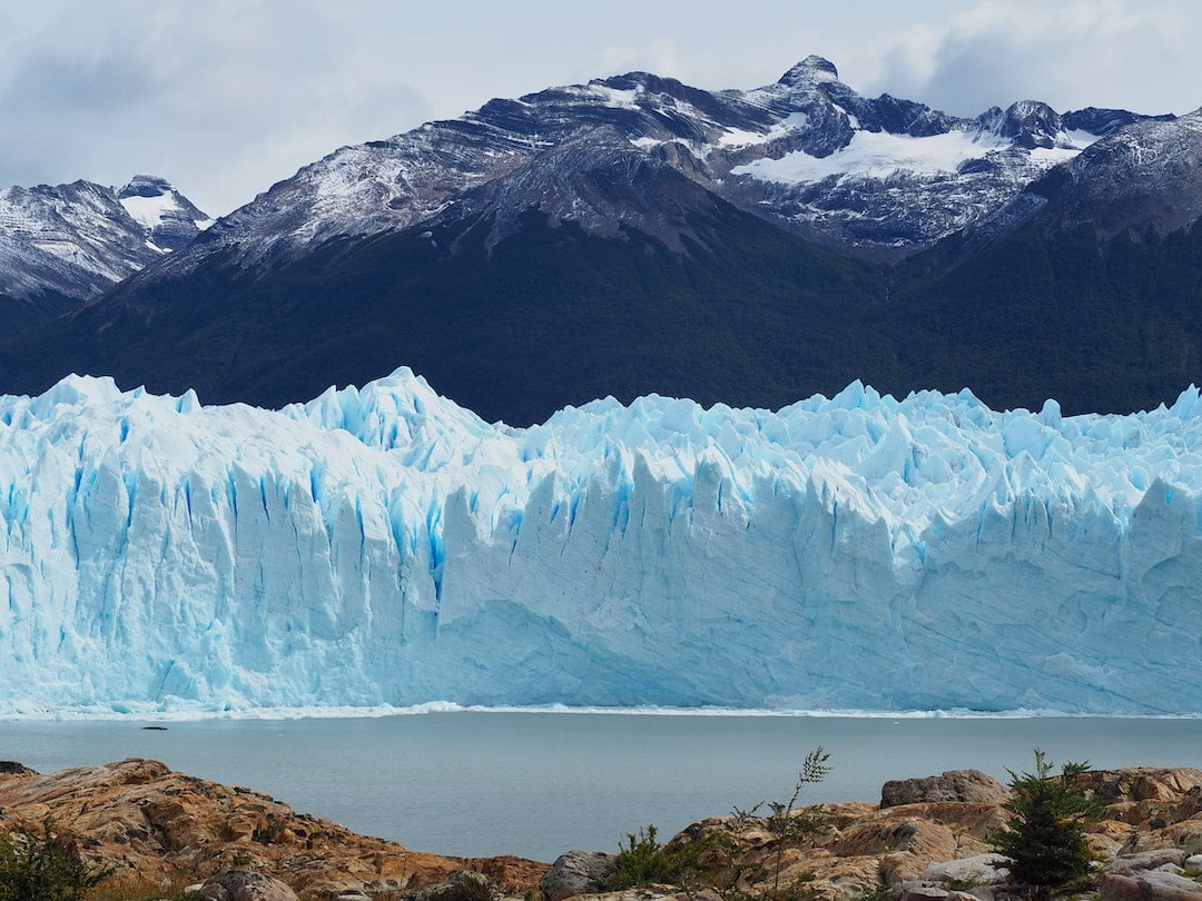 A wall of ice behind an expanse of water in front and mountains in the background