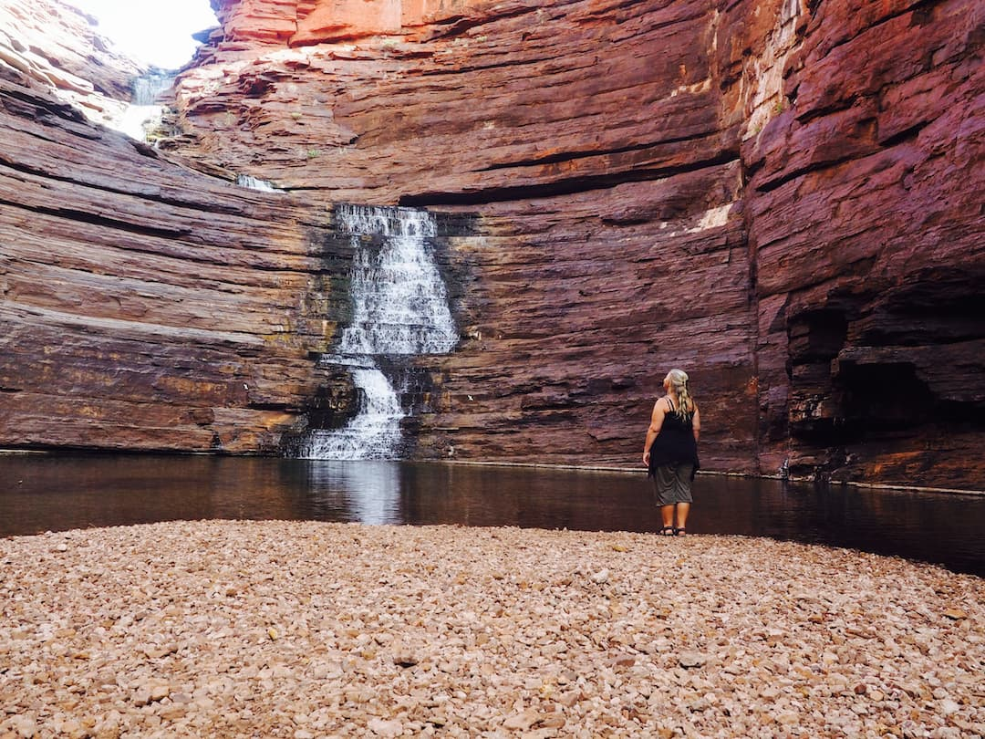 Nicky stands on a gravel beach looking upward to a waterfall