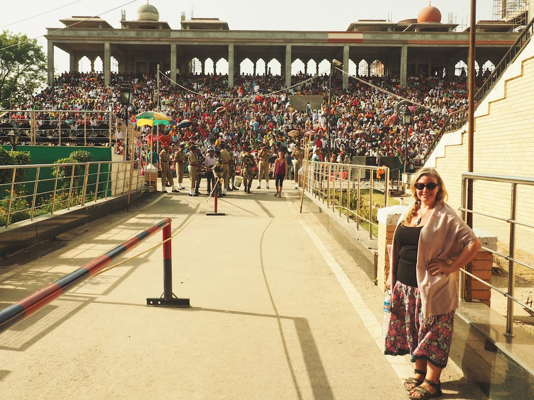 Nicky standing to the right of an entrance walkway with a grandstand in the background