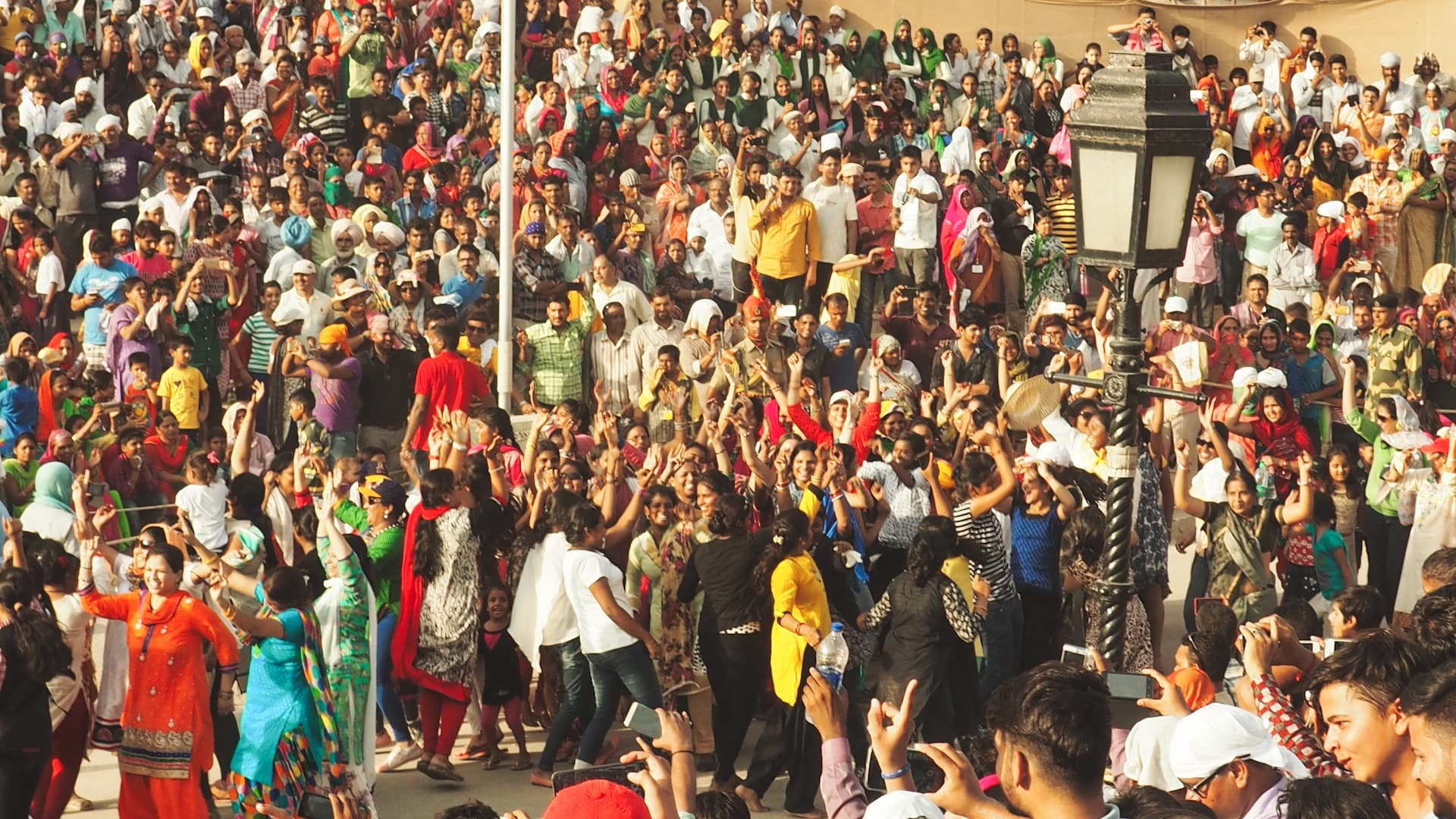 A crowd of people dancing with their arms in the air