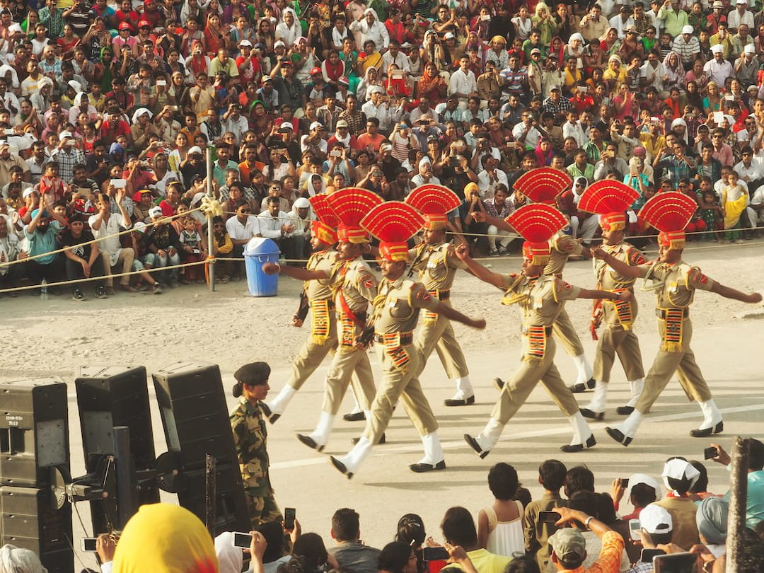 Eight soldiers in three rows march in front of a seated crowd