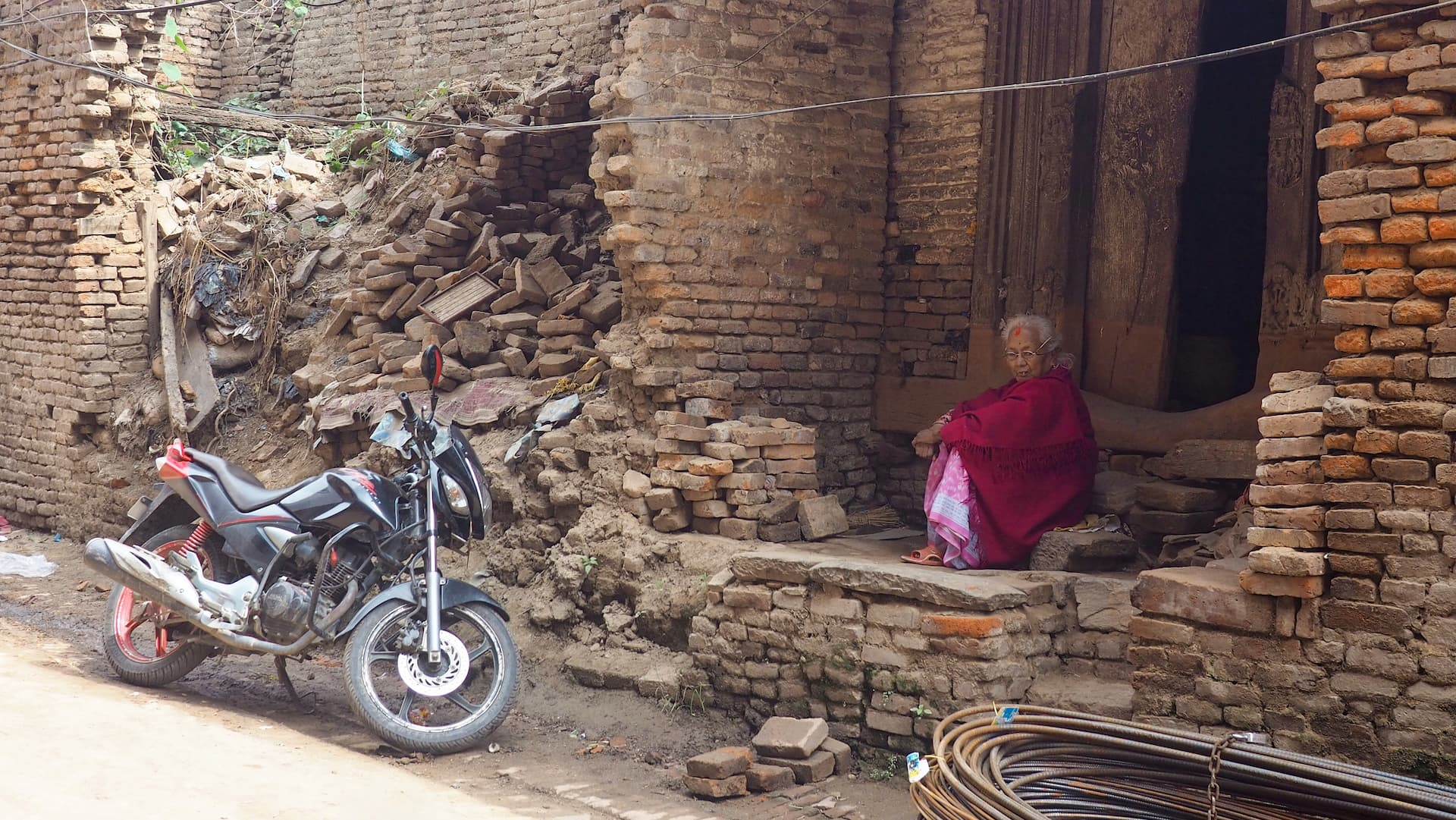 A woman in red clothing sits in a doorstep next to rubble and a motorcycle