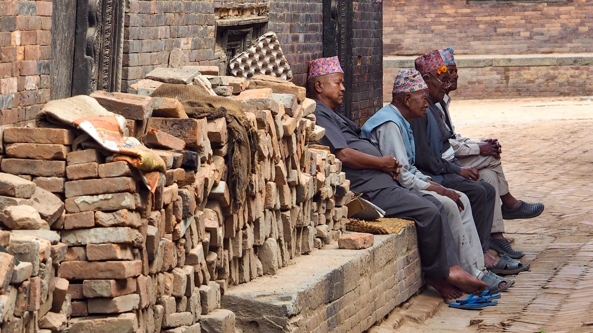 A pile of bricks in the foreground lead to four men sitting at the side of a street
