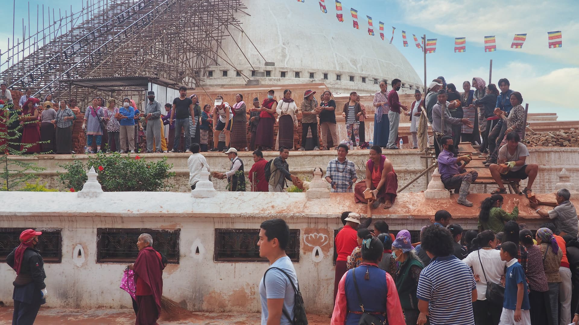 People standing around the Boudha Stupa passing building materials to one another