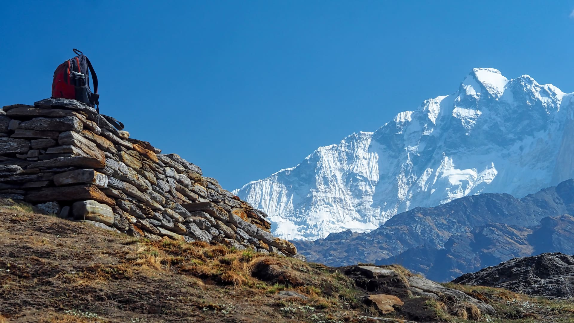 An orange backpack on a wall (left) and white snow-capped mountains (right)