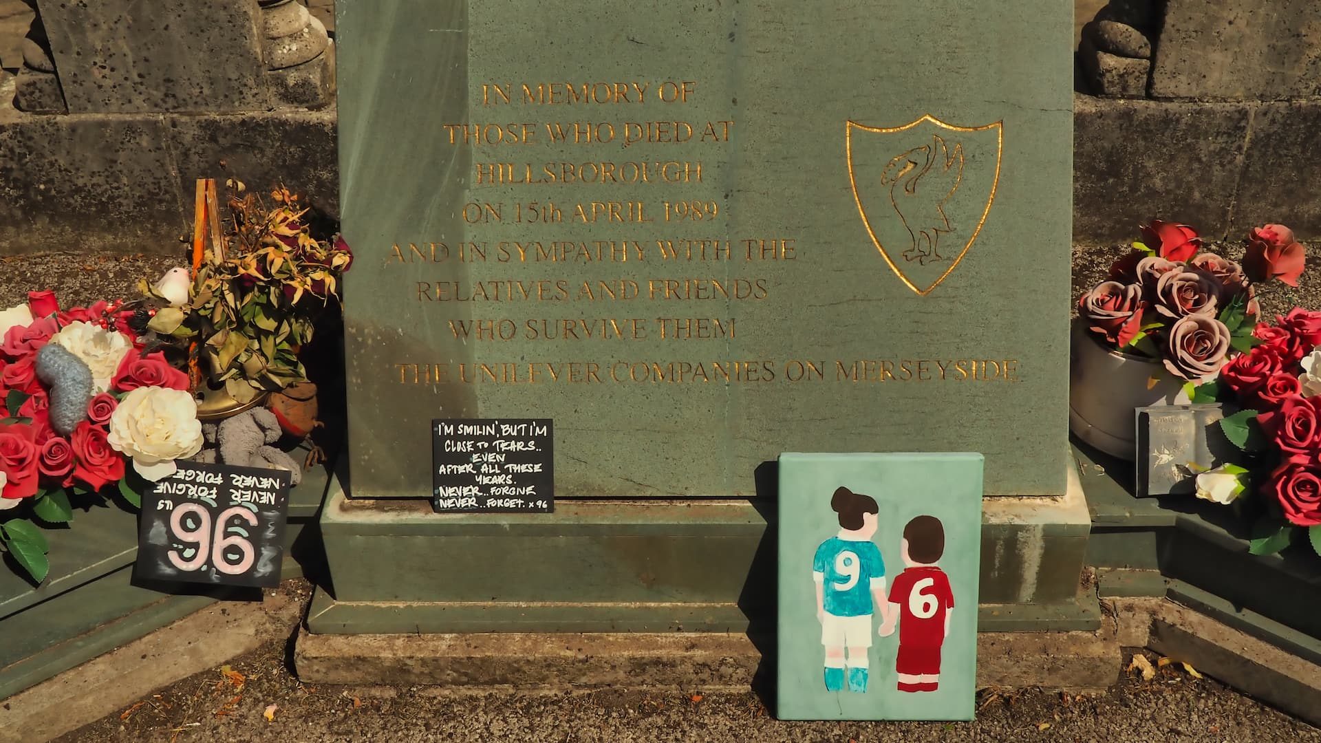 Flowers places on each side of a stone plaque and a drawing of two figures in blue and red football kits