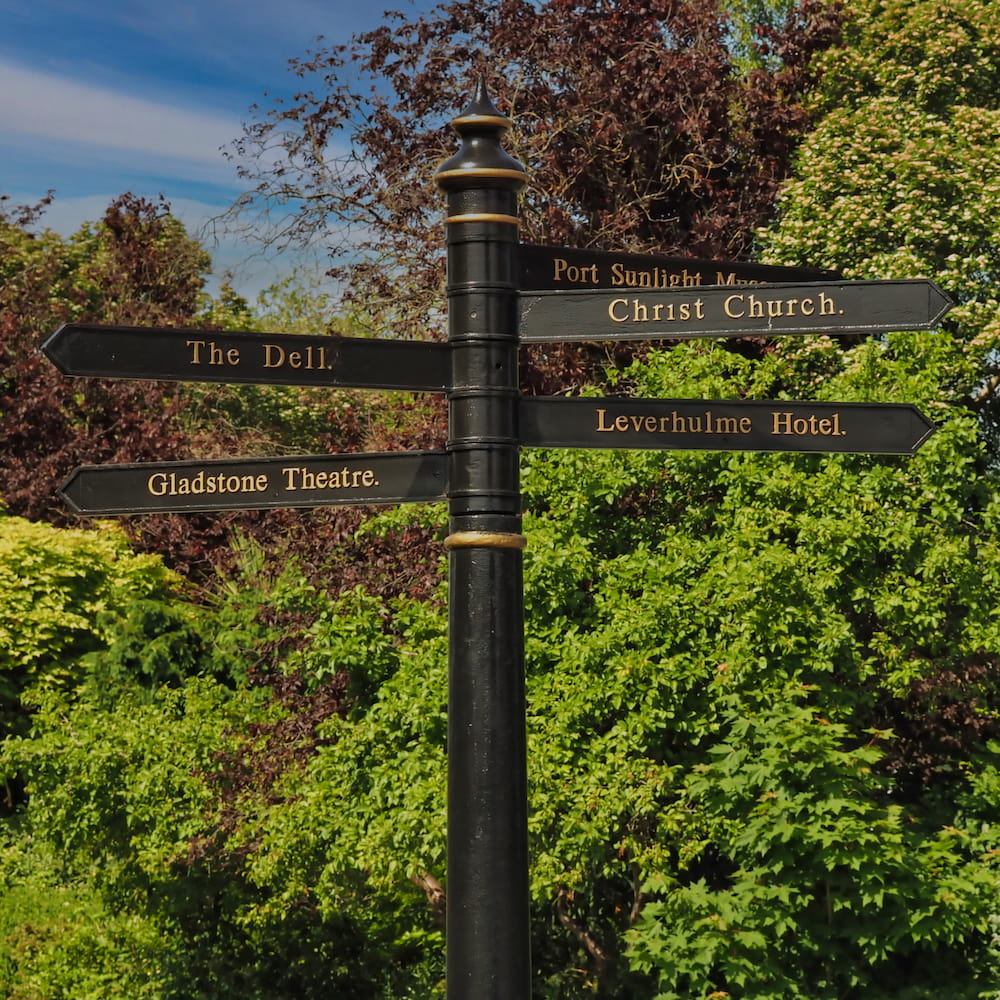 A black signpost with numerous directions