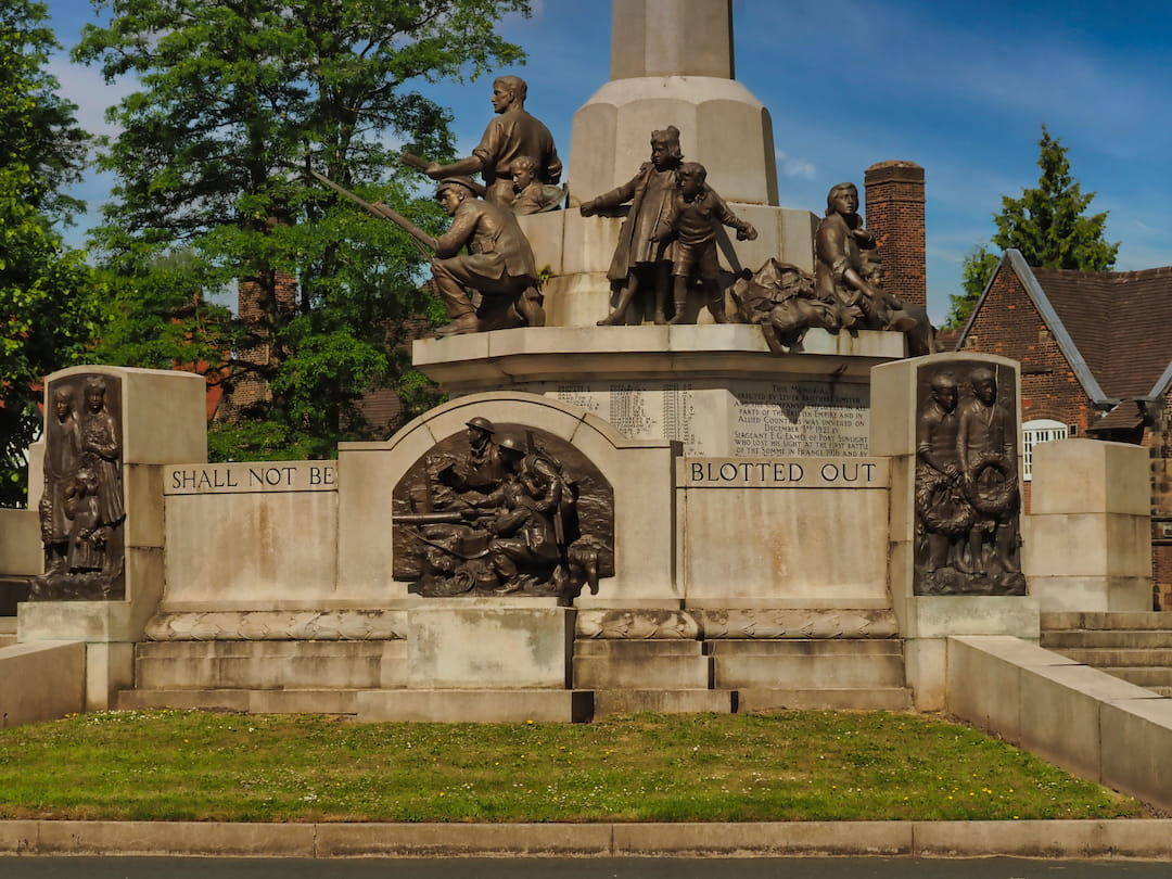 A stone memorial with bronze statues and plaques