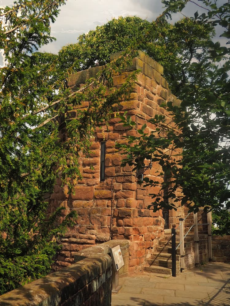 A sandstone tower stands amongst trees