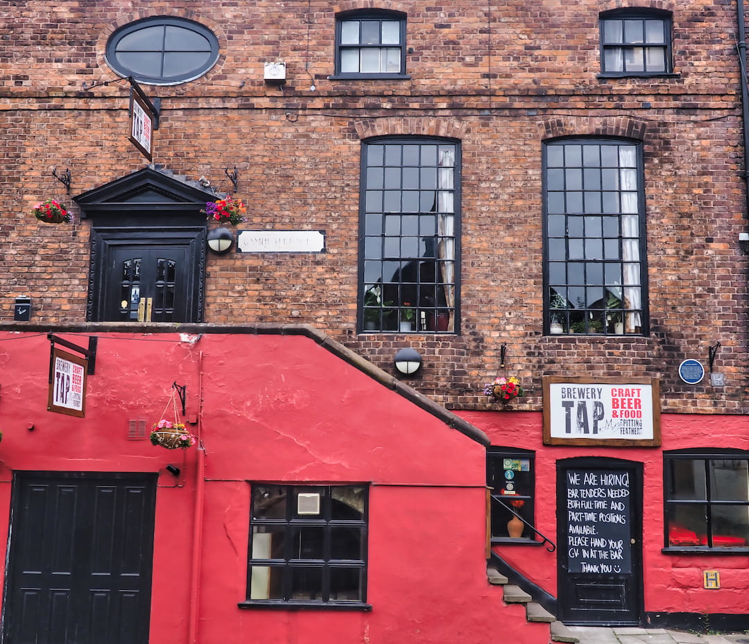 A red wall hides steps leading up to a door on a red bricked building