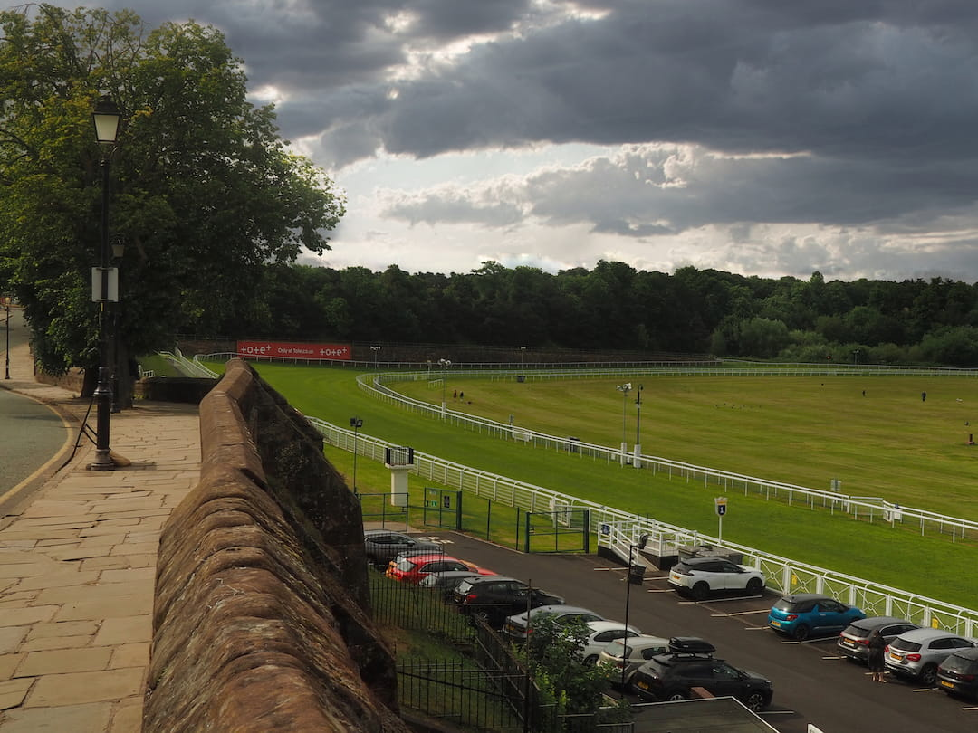 A path and a wall runs along  to the left overlooking a racecourse to the right