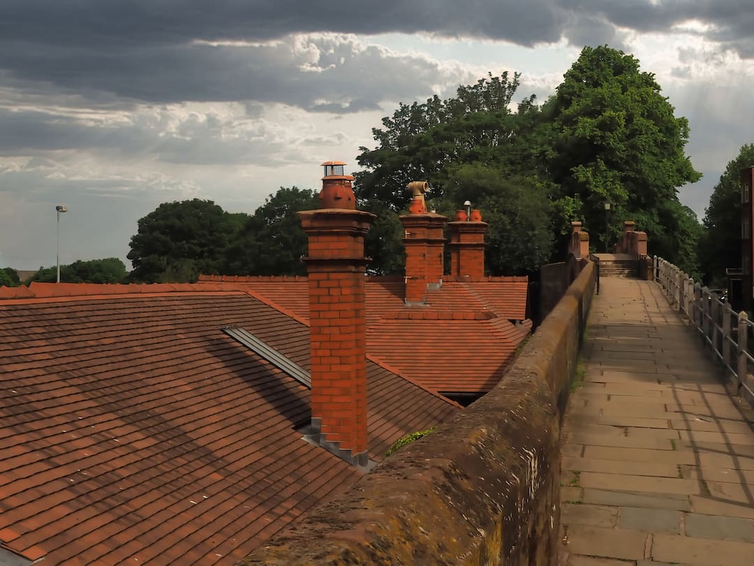 Red rooftops with chimneys to the left, a wall and footpath to the right