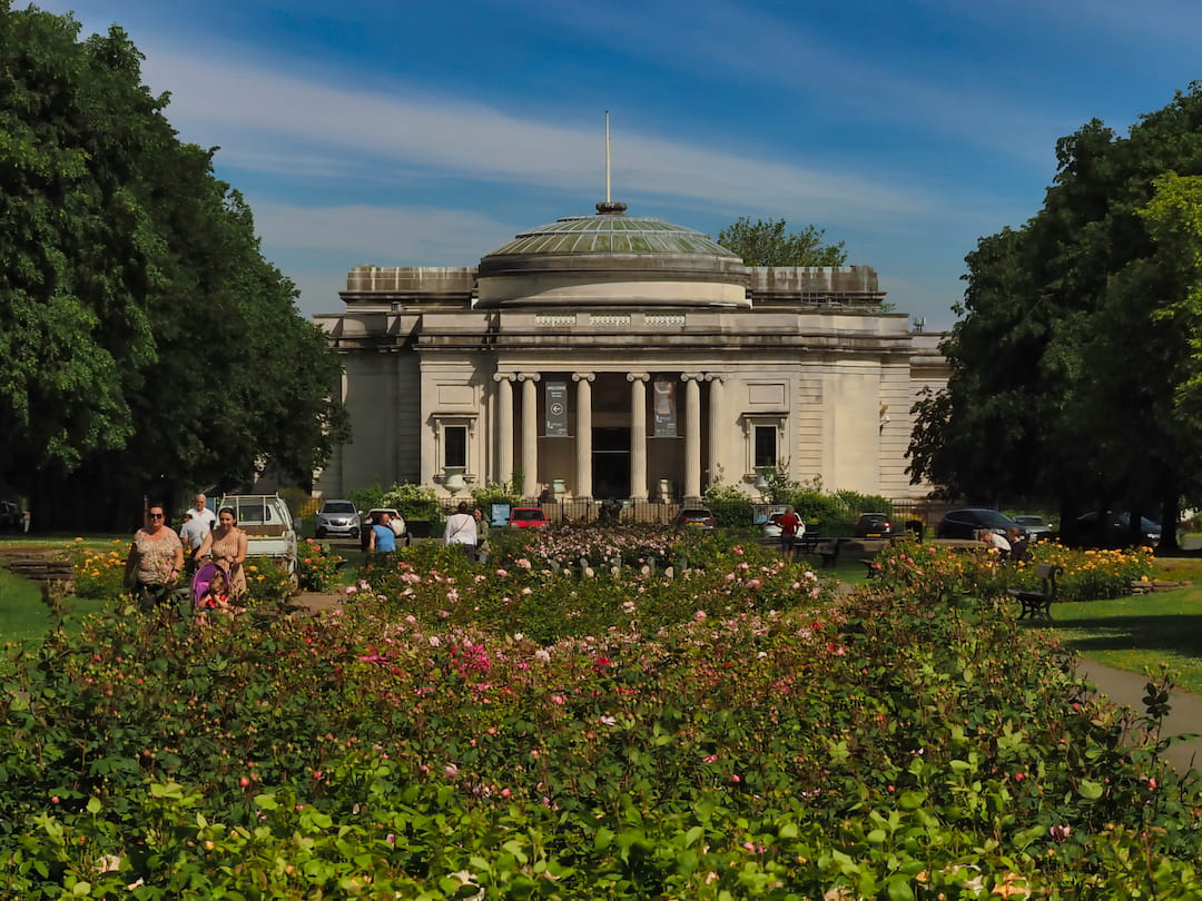 A building with pillars in the background and a flower garden in the foreground leading to it