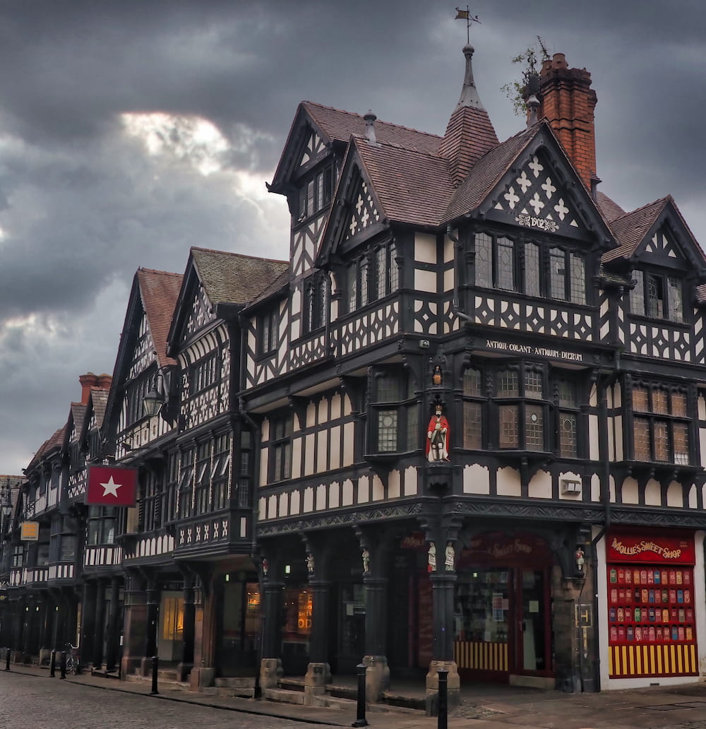 A black and white half-timbered building with paved archway on the ground floor