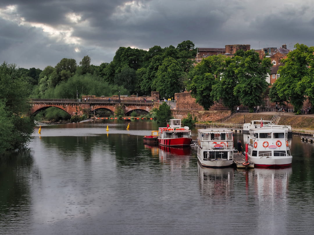 Two boats moored on a river with a stone bridge in the background