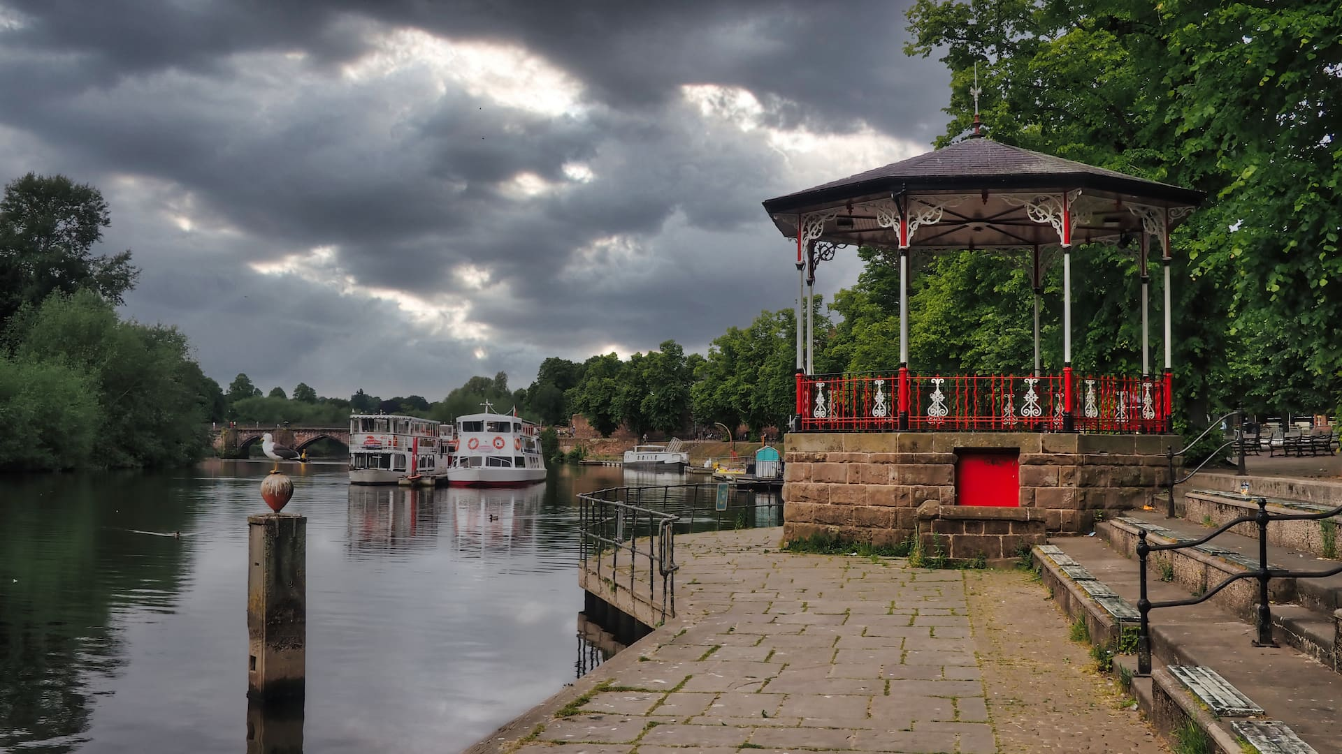 A red pagoda in the foreground stands next to a river with two boats in the background
